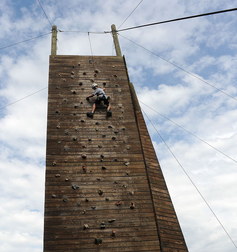 A Manitou camper has almost reached the top of the climbing tower