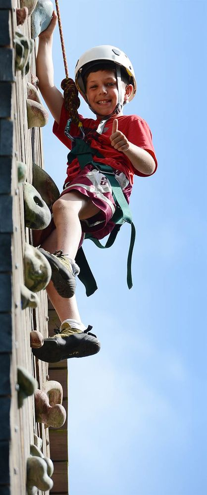 A young boy climbs the climbing wall at Camp Manitou