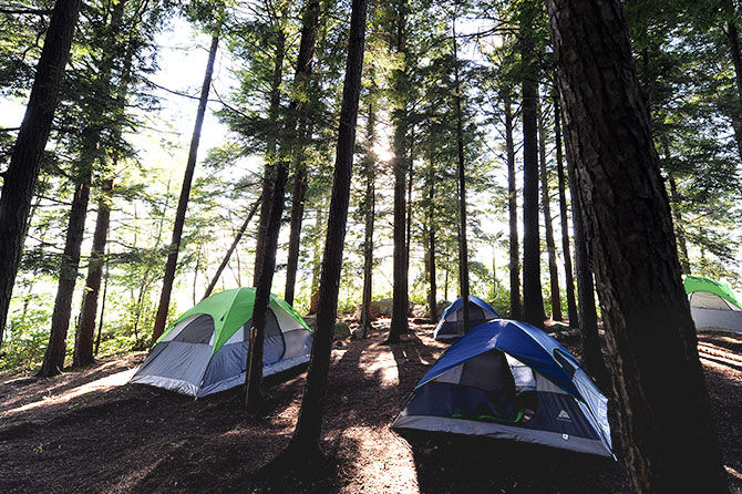 Tents sit in the woods of Camp Manitou's island camp site