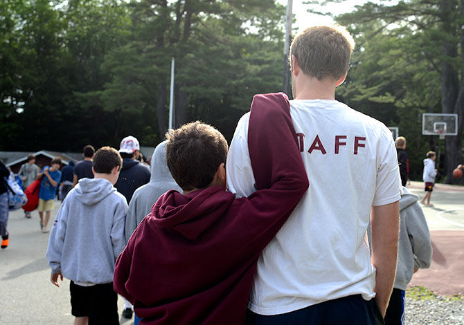 A camper puts his arm around a staff member's shoulders