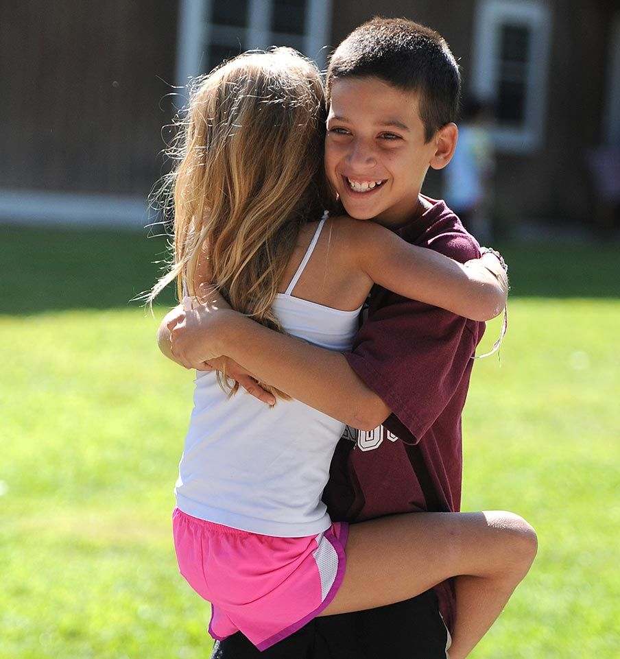 A sister hugs her brother at Camp Manitou during Visiting Day