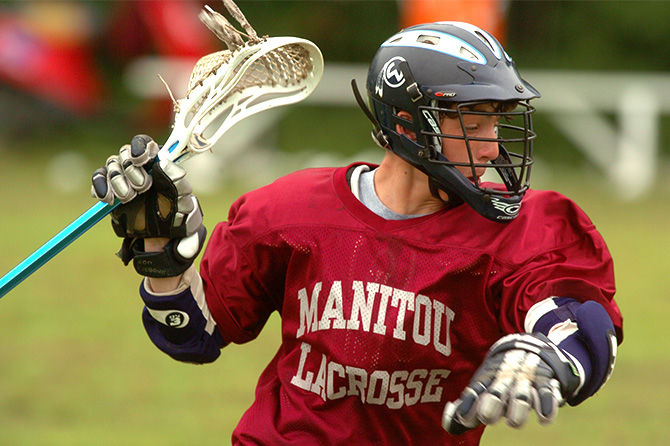A camper plays lacrosse at Camp Manitou for Boys