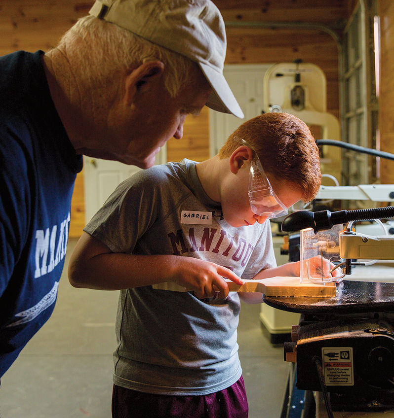 A woodworking instructor watches closely as a camper crafts a masterpiece in the carpentry shop