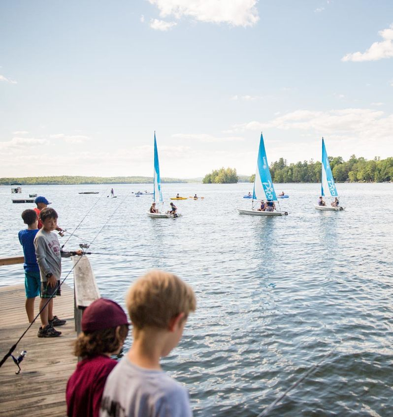 Campers fish in the lake while other sail on the sparkling water