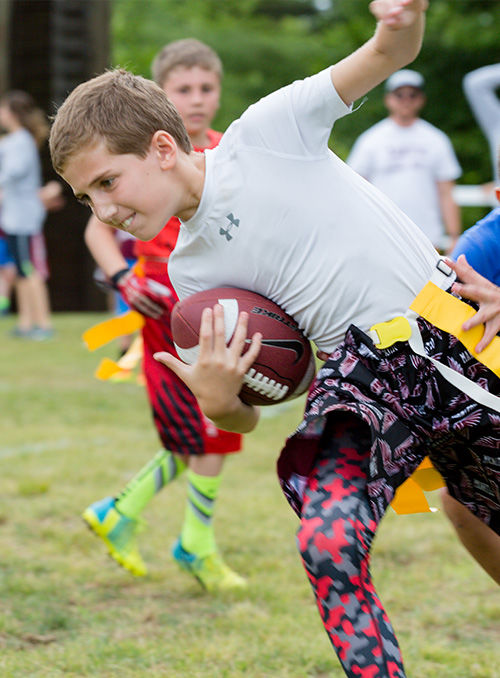 Campers play flag football at Camp Manitou