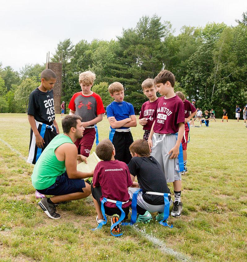 A staffer talks his team through football plays