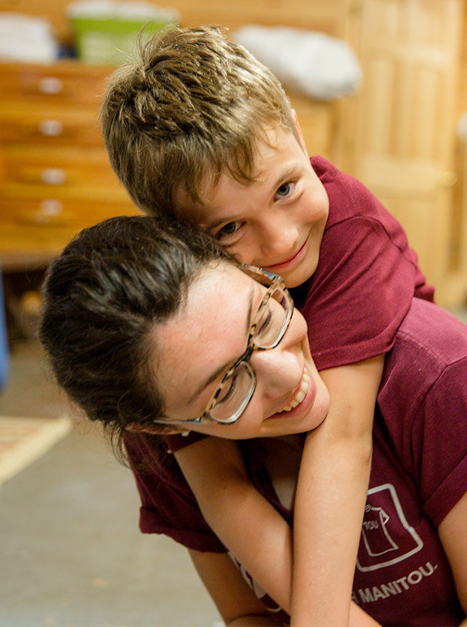 A camper at Manitou hugs his counselor