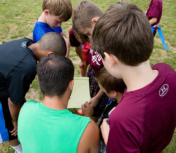 Campers study football plays with their counselor