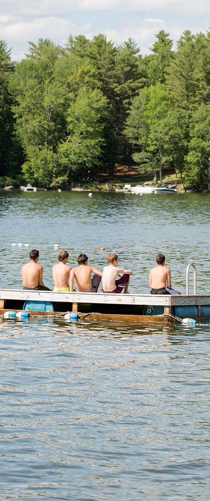 Five boys set on a floating dock in East Lake, looking back at Camp Manitou